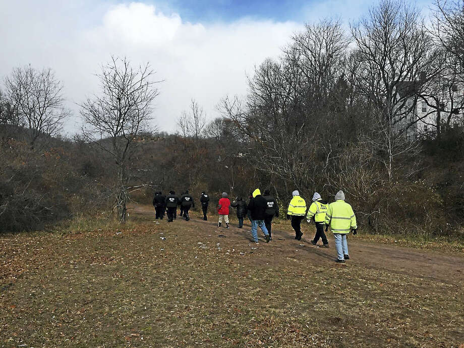New Haven police officers and others walk into a homeless camp off of Interstate 91 Thursday to check for people, weapons and hazardous waste before the city removed tarps, tents, personal belongings and trash from the site. Photo: Anna Bisaro — New Haven Register