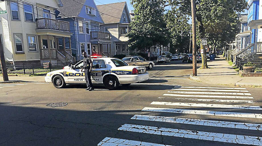 A New Haven police officer stands guard and blocks the street where a young man was gunned down early Saturday morning. Photo: Brian Zahn — New Haven Register