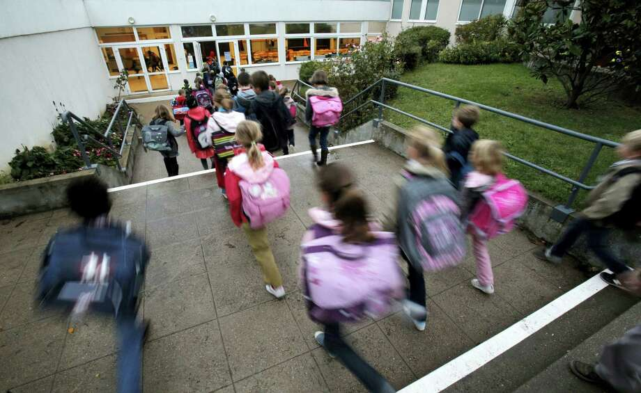 In this Oct. 5, 2012, file photo, students enter school of La Ronce in Ville d'Avray, west of Paris. France's government has unveiled Wednesday Aug. 24, 2016, a plan to teach children how to react in case of an attack at school. Every school will have to organize three security drills per year, including one based on the scenario of an attack with at least one assailant inside the building. Photo: AP Photo/Christophe Ena    / Copyright 2016 The Associated Press. All rights reserved. This material may not be published, broadcast, rewritten or redistribu