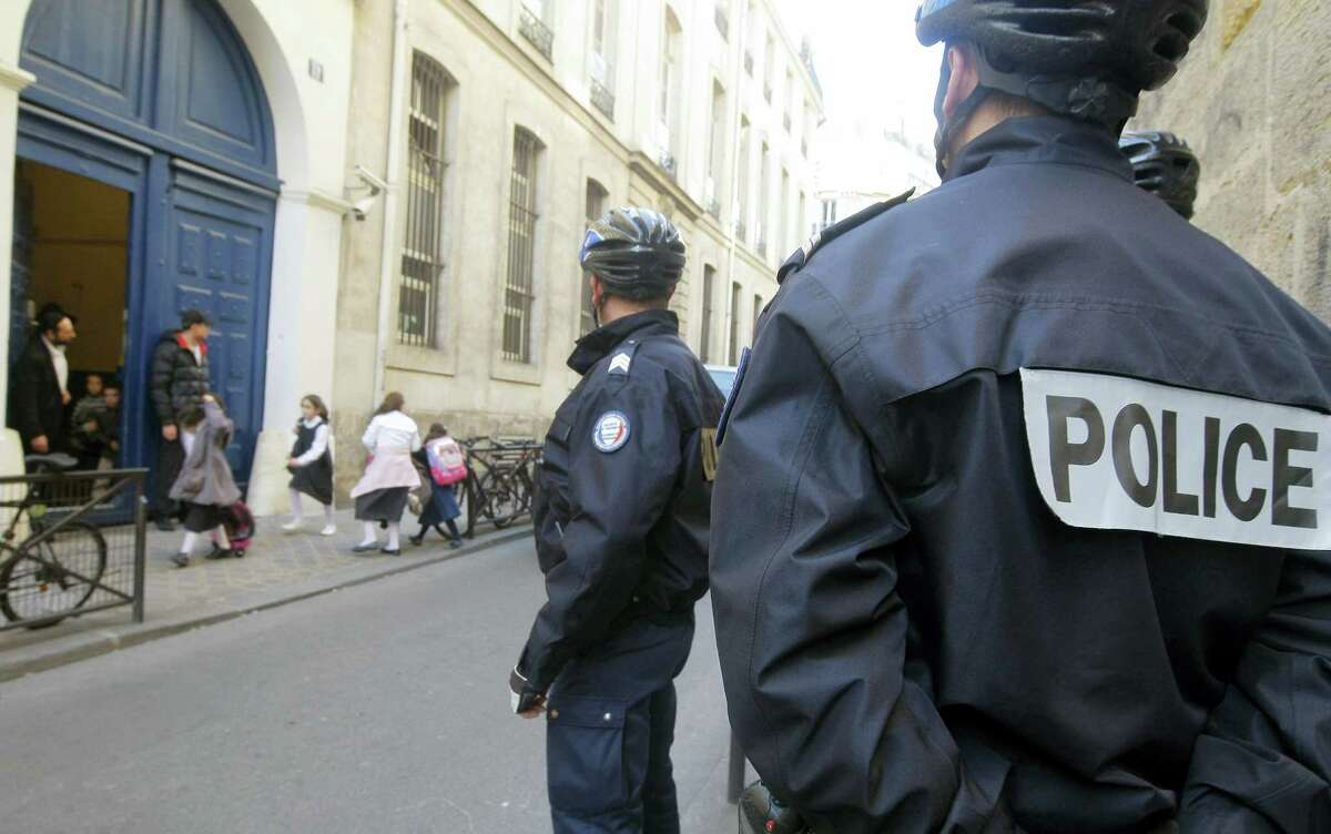 In this March 19, 2012, file photo, schoolchildren leave a Jewish school in Paris watched by police officers after an attack on one in Toulouse, in southwest France. France's government has unveiled Wednesday Aug. 24, 2016, a plan to teach children how to react in case of an attack at school. French Education Minister Najat Vallaud-Belkacem recalled Islamic radical Mohamed Merah's attack on a Jewish school in 2012 in Toulouse.