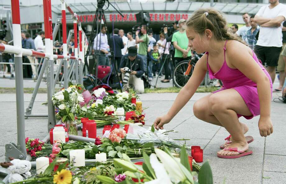 A girl puts down flowers in front of the Olympia shopping center were a shooting took place leaving nine people dead the day before on Saturday, July 23, 2016, in Munich, Germany. Photo: AP Photo/Sebastian Widmann    / AP