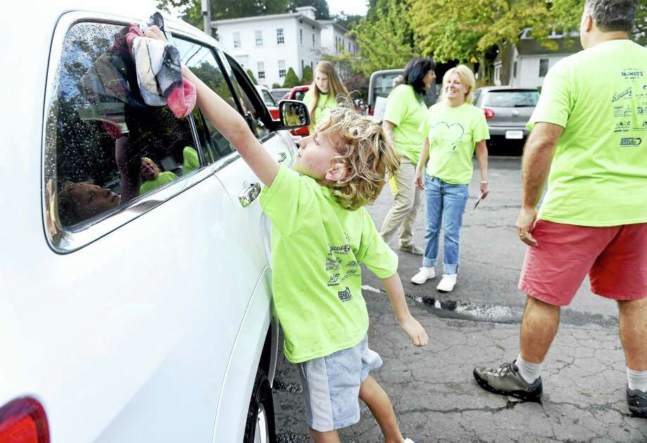Eight-year-old Grady Pascucilla helps dry a car during a car wash fundraiser for St. Jude Children's Hospital at Palumbo's Automotive in Guilford Saturday. Photo: Arnold Gold — New Haven Register
