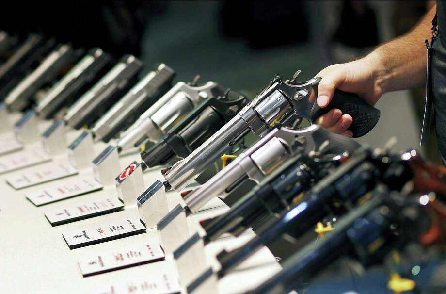 In this Jan. 19, 2016 file photo, handguns are displayed at the Smith & Wesson booth at the Shooting, Hunting and Outdoor Trade Show in Las Vegas. Nearly two-thirds of Americans expressed support for stricter gun laws, according to an Associated Press-GfK poll released Saturday, July 23, 2016. A majority of poll respondents oppose banning handguns. Photo: AP Photo/John Locher, File    / Copyright 2016 The Associated Press. All rights reserved. This material may not be published, broadcast, rewritten or redistribu