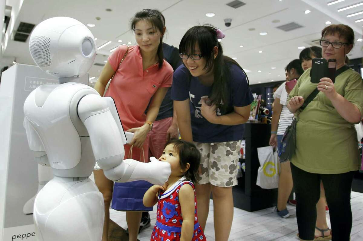 """Shoppers talk to SoftBank Corp.'s companion robot Pepper at a store in Tokyo recently. Pepper robots, equipped with a """"heart"""" designed to not only recognize human emotions but react with simulations of anger, joy and irritation, are on sale."""