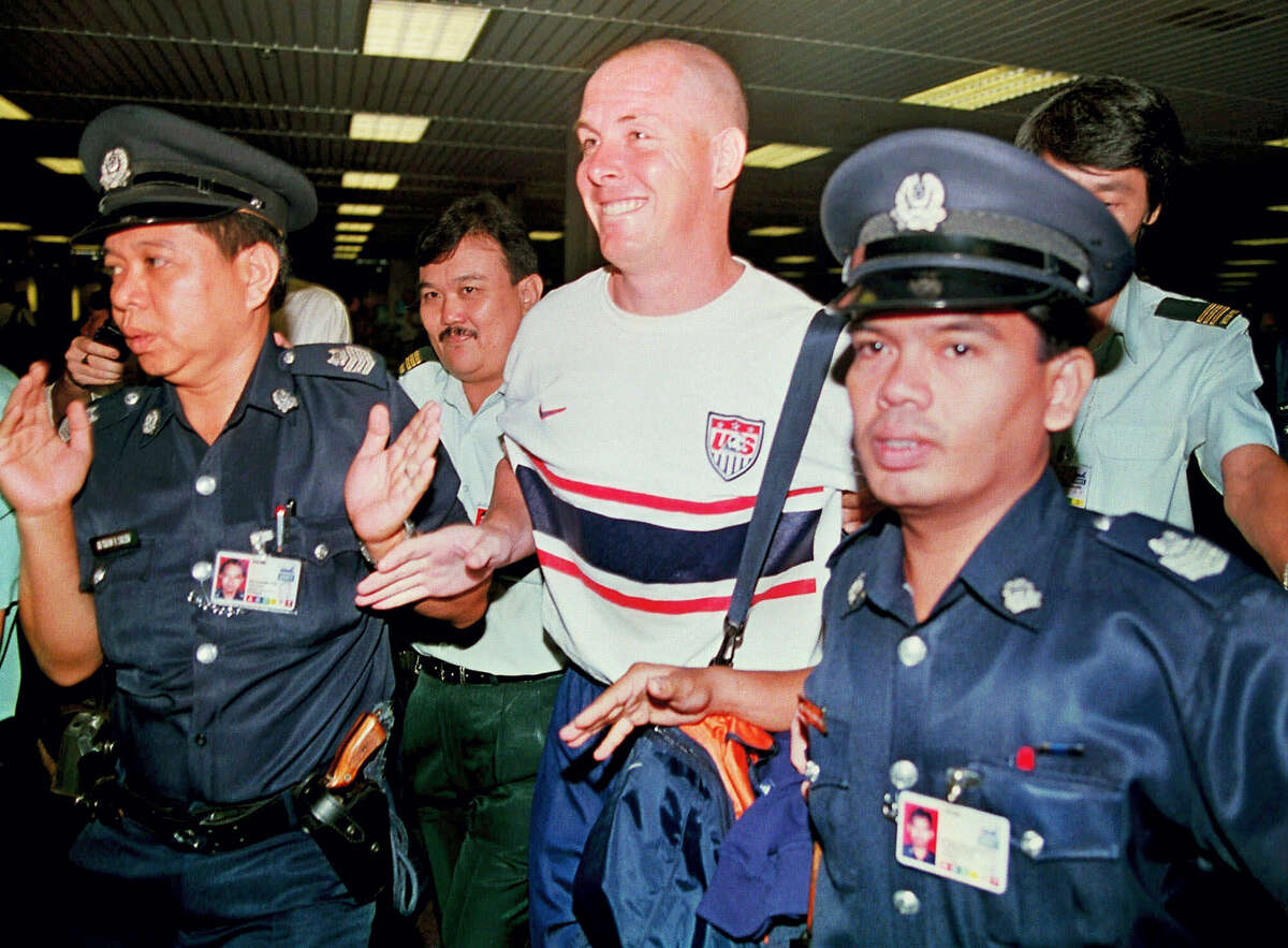 Former Barings bank trader Nick Leeson, center, is led through immigration by Singapore police officials at Changi airport shortly after he was freed from prison in Singapore. The British trader, who caused the collapse of Barings Bank in 1995 when he lost more than $1 billion in unauthorized trades, was released from a Singapore jail after serving 3½ years.