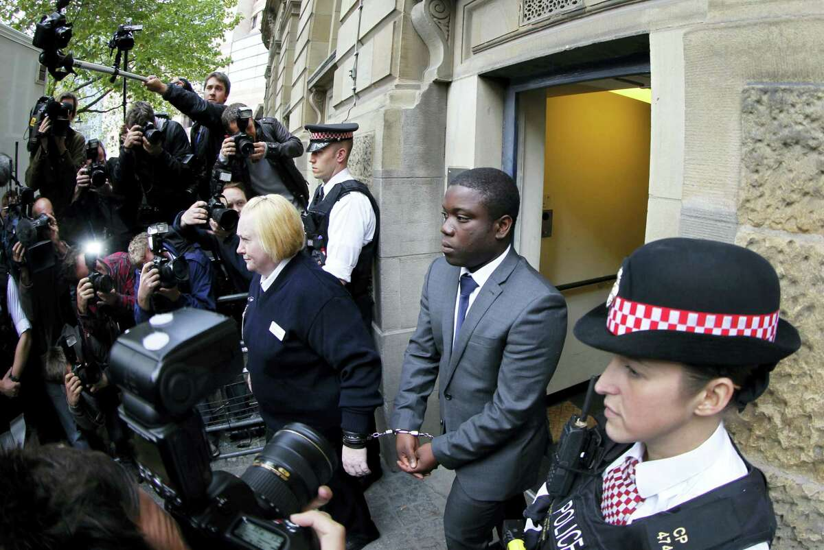 City trader Kweku Adoboli, second right, leaves the City of London Magistrates' Court in London. The former trader, who cost Swiss bank UBS 1.4 billion pounds, has been fighting deportation to his native Ghana since being released from prison in 2015.