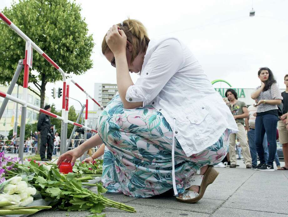 A woman lights a candle in front of the Olympia shopping center where a shooting took place leaving nine people dead the day before in Munich, Germany, Saturday, July 23, 2016. Photo: AP Photo — Jens Meyer / Copyright 2016 The Associated Press. All rights reserved. This material may not be published, broadcast, rewritten or redistribu