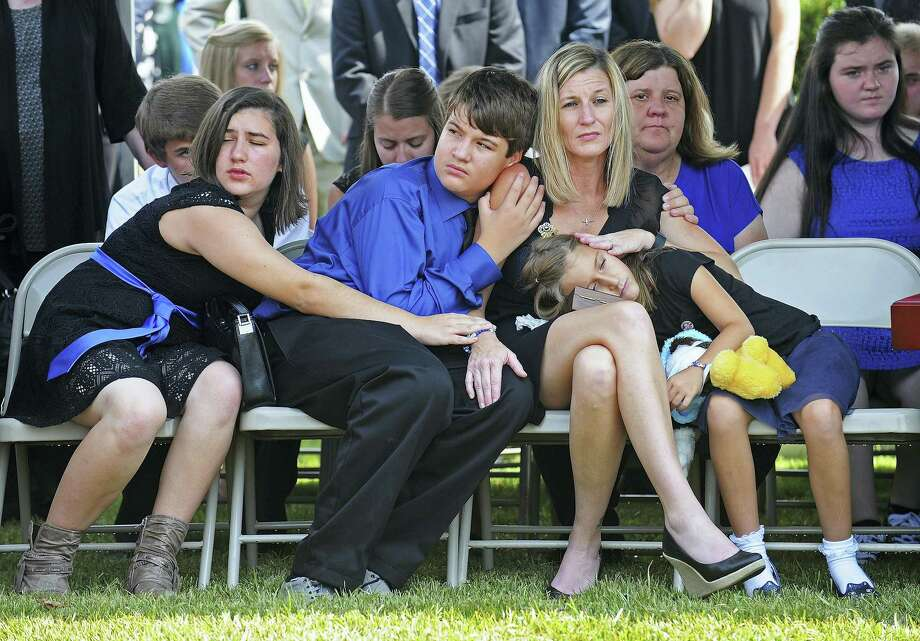 Tonja Garafola, the widow of East Baton Rouge Sheriff deputy Brad Garafola mourns with her children during his funeral at the Istrouma Baptist Church in Baton Rouge, La., Saturday, July 23, 2016. Multiple police officers were killed and wounded Sunday morning in a shooting near a gas station in Baton Rouge, less than two weeks after a black man was shot and killed by police here, sparking nightly protests across the city. Photo: Hilary Scheinuk — Baton Rouge Advocate Via AP, Pool / POOL Baton Rouge Advocate