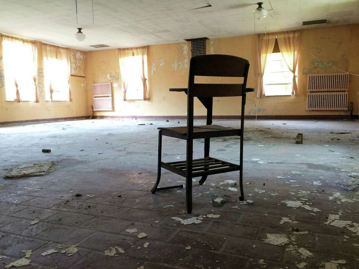 A classroom desk sits inside an abandoned building at the former Mansfield Training School.