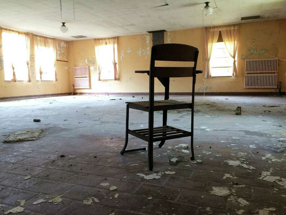 A classroom desk sits inside an abandoned building at the former Mansfield Training School. Photo: Pat Eaton-Robb — The Associated Press   / Copyright 2016 The Associated Press. All rights reserved.