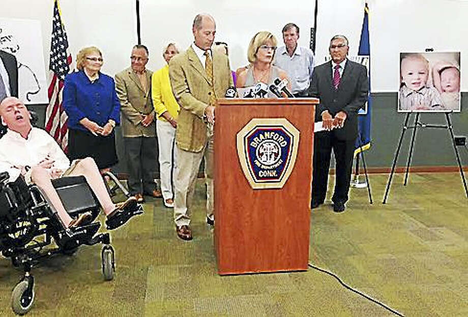 John and Jean Kelley are shown at the podium at the Branford Fire Department on Wednesday with Brian at the left and legislators lined up behind. Photo: Jack Kramer / CTNewsJunkie