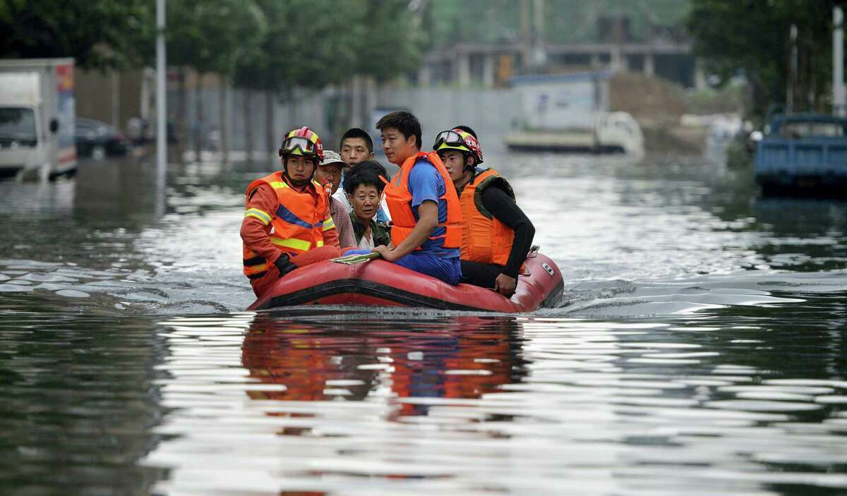 In this Thursday, July 21, 2016, photo, rescuers use a raft to transport people along a flooded street in Shenyang in northeastern China's Liaoning Province. Dozens of people have been killed and dozens more are missing across China after a round of torrential rains swept through the country earlier this week, flooding streams, triggering landslides and destroying houses.