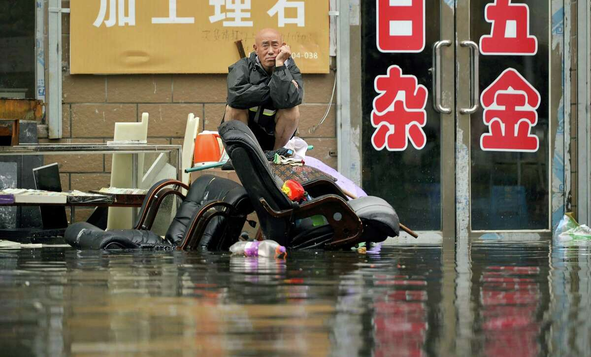 In this Thursday, July 21, 2016 photo, a man sits outside of a flooded shop in Shenyang in northeastern China's Liaoning Province. Dozens of people have been killed and dozens more are missing across China after a round of torrential rains swept through the country earlier this week, flooding streams, triggering landslides and destroying houses.