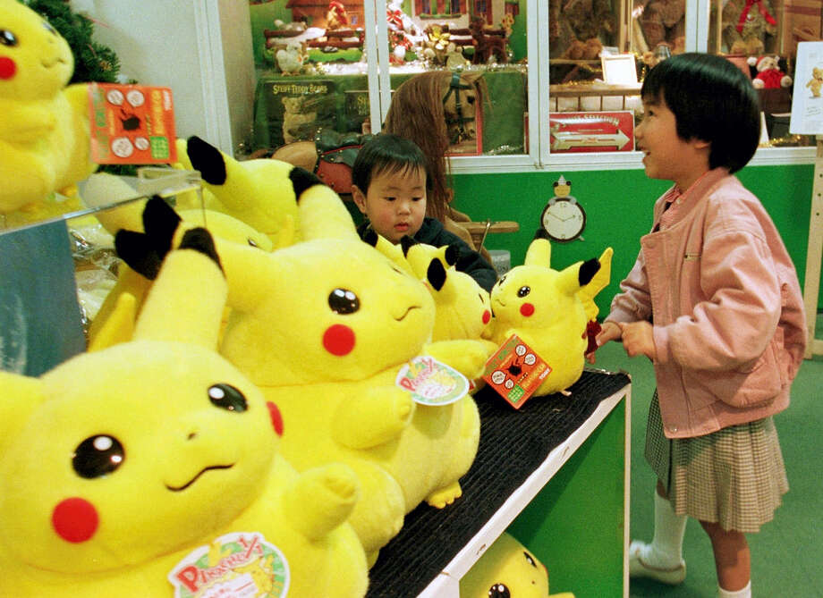 """A girl and her brother view dolls of a Pokemon cartoon character at a toy shop in Tokyo's Ginza shopping district. A survey shows about 90 percent of adults who have downloaded the new """"Pokemon Go"""" smartphone game in 2016, which lets you find cartoon monsters in the real world, are between 18 and 34-years-old, many who are old enough to have fallen in love with Pokemon the first time around. Photo: Naokazu Oinuma — The Associated Press File   / AP1997"""