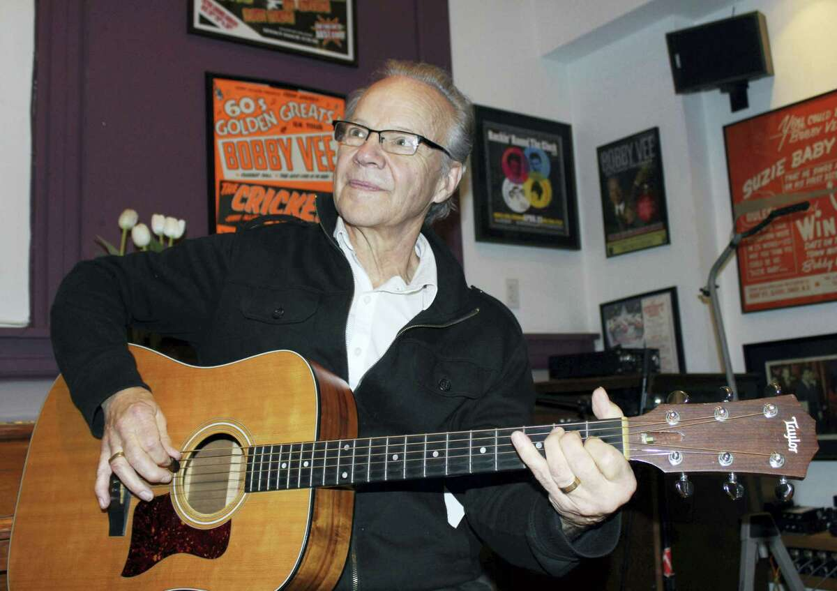 In this Dec. 18, 2013 photo, Bobby Vee plays the guitar at his family's Rockhouse Productions in St. Joseph, Minn. Vee, whose rise toward stardom began as a 15-year-old fill-in for Buddy Holly after Holly was killed in a plane crash, died Oct. 24, 2016 of complications from Alzheimer's disease. He was 73.