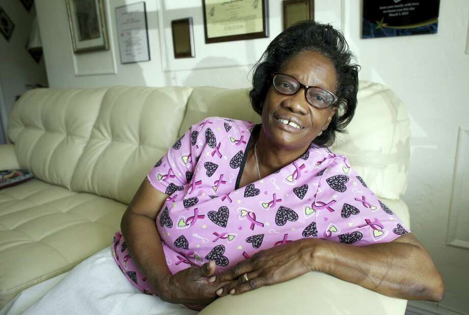 In this photo taken Oct. 18, 2016, Gwen Strowbridge, 71, poses for a photograph wearing her work uniform at her home in Deerfield Beach, Fla. Strowbridge works six days a week caring for a 100-year-old woman. She has worked all her life and plans to work until she can't physically work anymore. Photo: AP Photo/Lynne Sladky   / Copyright 2016 The Associated Press. All rights reserved.