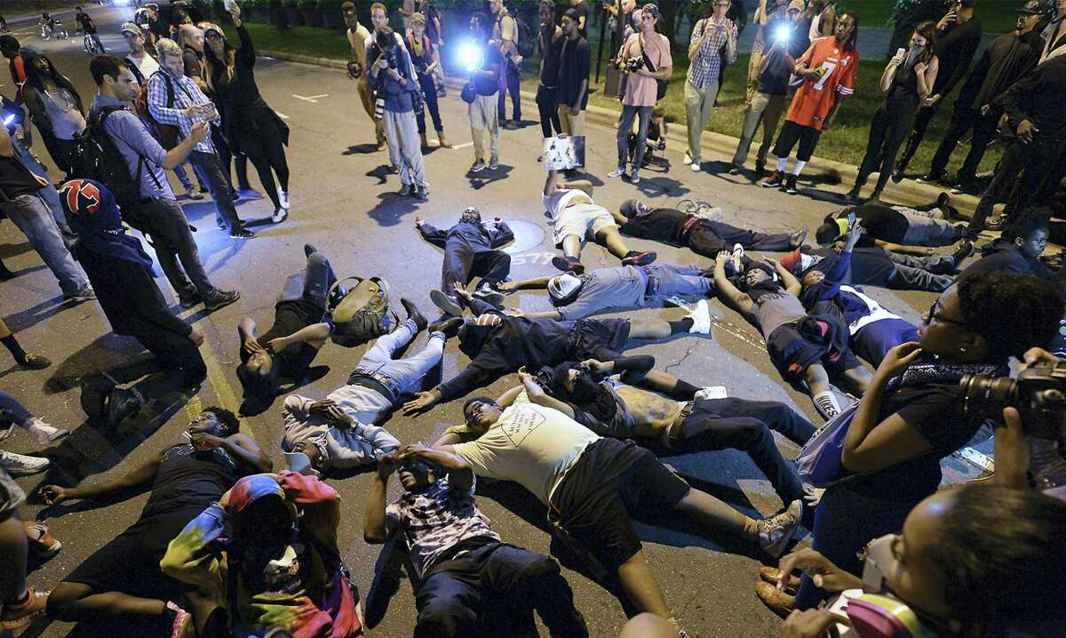 Protesters block the road in front of Bank of America Stadium in Charlotte, N.C. on Thursday, Sept. 22, 2016. The curfew has ended for Friday in Charlotte following a night of mostly peaceful protests of the shooting of Keith Lamont Scott by an officer. Charlotte Mayor Jennifer Roberts issued the curfew order Thursday night, to be in effect from midnight until 6 a.m. each day that the state of emergency continues.