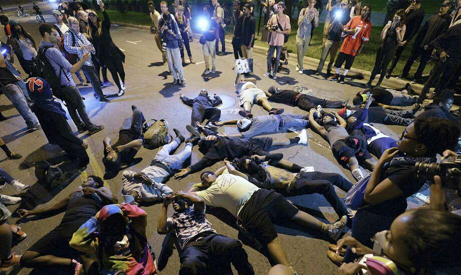 Protesters block the road in front of Bank of America Stadium in Charlotte, N.C. on Thursday, Sept. 22, 2016.  The curfew has ended for Friday in Charlotte following a night of mostly peaceful protests of the shooting of Keith Lamont Scott by an officer. Charlotte Mayor Jennifer Roberts issued the curfew order Thursday night, to be in effect from midnight until 6 a.m. each day that the state of emergency continues. Photo: Jeff Siner/The Charlotte Observer Via AP    / The Charlotte Observer
