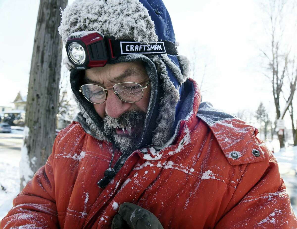 In this Monday photo, ice forms in Carl Bentson's beard and mustache as he clears sidewalks near Colborne Street and St. Clair Avenue in St. Paul, Minn. Temperatures dipped below zero for the first time this winter and will hover near there for most of the week.