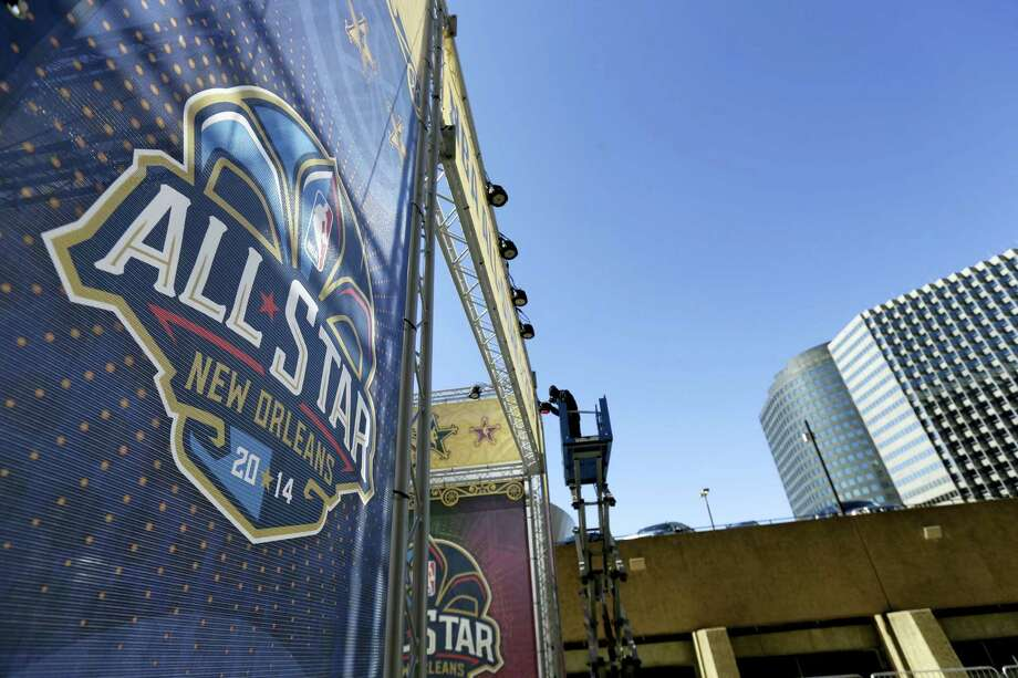 In this 2014 file photo, a worker attaches a banner to a scaffolding in New Orleans in preparation of the NBA All-Star Game. Photo: The Associated Press File Photo   / Copyright 2016 The Associated Press. All rights reserved. This material may not be published, broadcast, rewritten or redistribu
