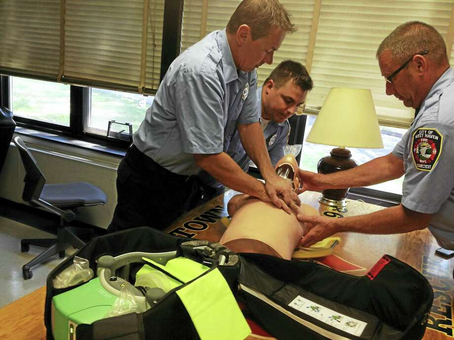 City of West Haven Fire Department — Allingtown paramedic Chris Shore, left, paramedic Paul Martus, center, and EMT Mike DiMassa demonstrate how to use the Lucas 2 chest compression system. Photo: MARK ZARETSKY — NEW HAVEN REGISTER