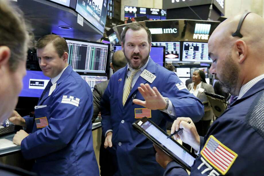 Specialist Charles Boeddinghaus, center, works with traders on the floor of the New York Stock Exchange Monday. Photo: Richard Drew — The Associated Press   / AP