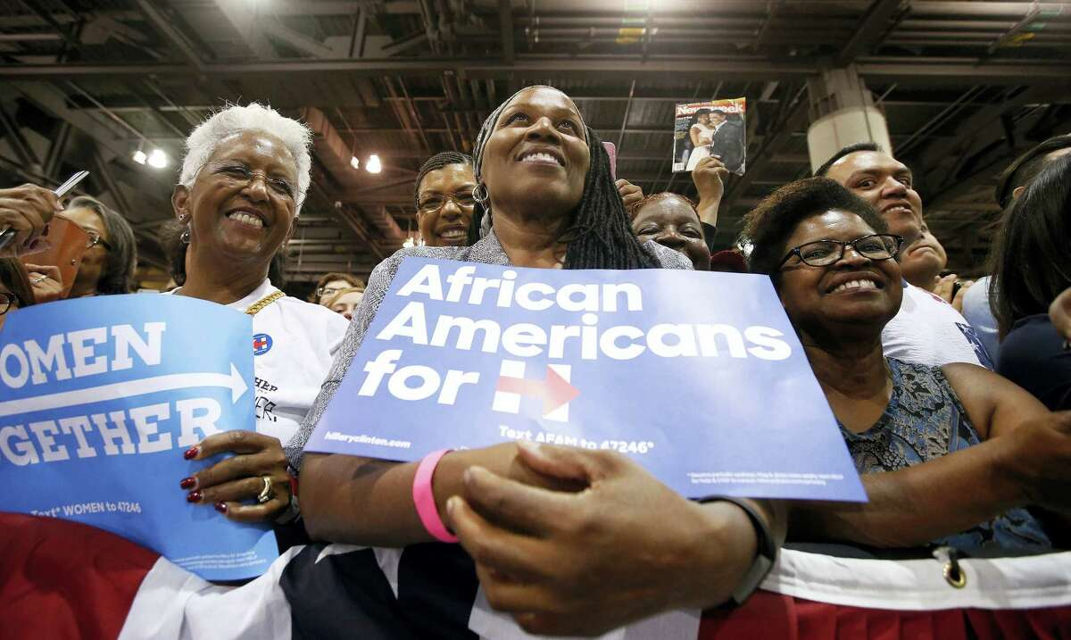 Supporters listen to first lady Michelle Obama as she speaks during a campaign rally for Democratic presidential candidate Hillary Clinton on Oct. 20, 2016 in Phoenix.