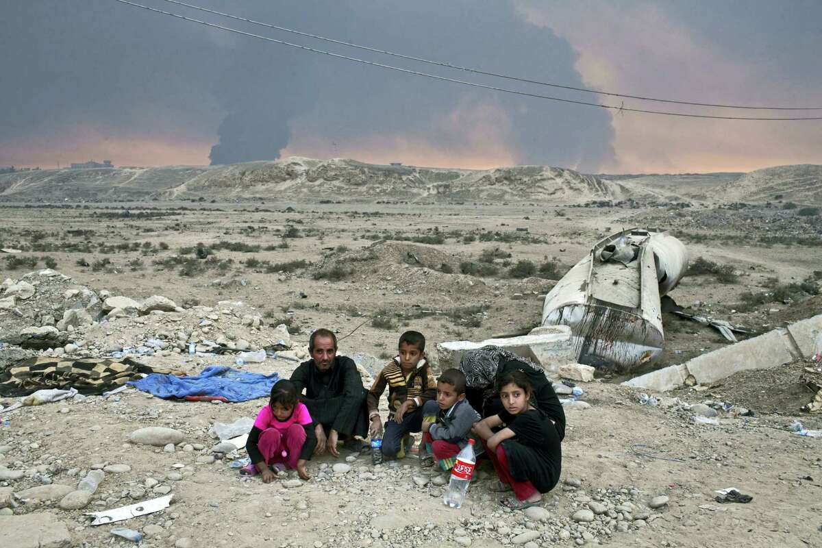 Internally displaced persons sit at a checkpoint as smoke rises from the burning oil wells in Qayyarah, about 31 miles (50 km) south of Mosul, Iraq on Oct. 23, 2016. Islamic State fighters torched a sulfur plant south of Mosul, sending a cloud of toxic fumes into the air that mingled with oil wells the militants had lit on fire to create a smoke screen.