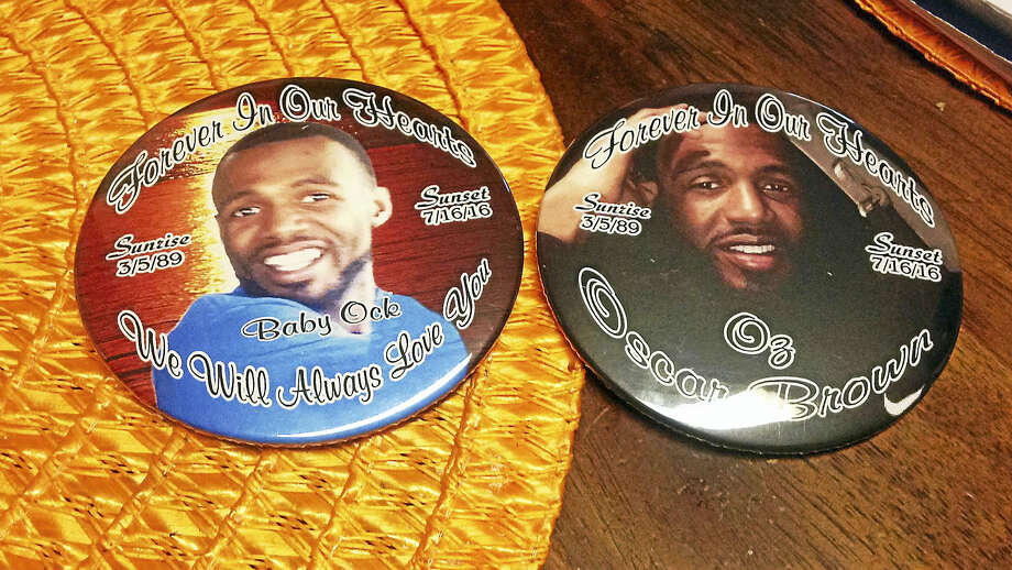 Tanya Williams-Richardson looks at buttons depicting her late son, Oscar Brown. Photo: Juliemar Ortiz — New Haven Register