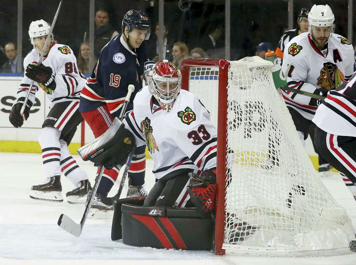 New York Rangers right wing Jesper Fast (19) knocks the puck into the net for a goal against Chicago Blackhawks goalie Scott Darling (33) during the second period Tuesday in New York. The Blackhawks edged the Rangers 2-1.