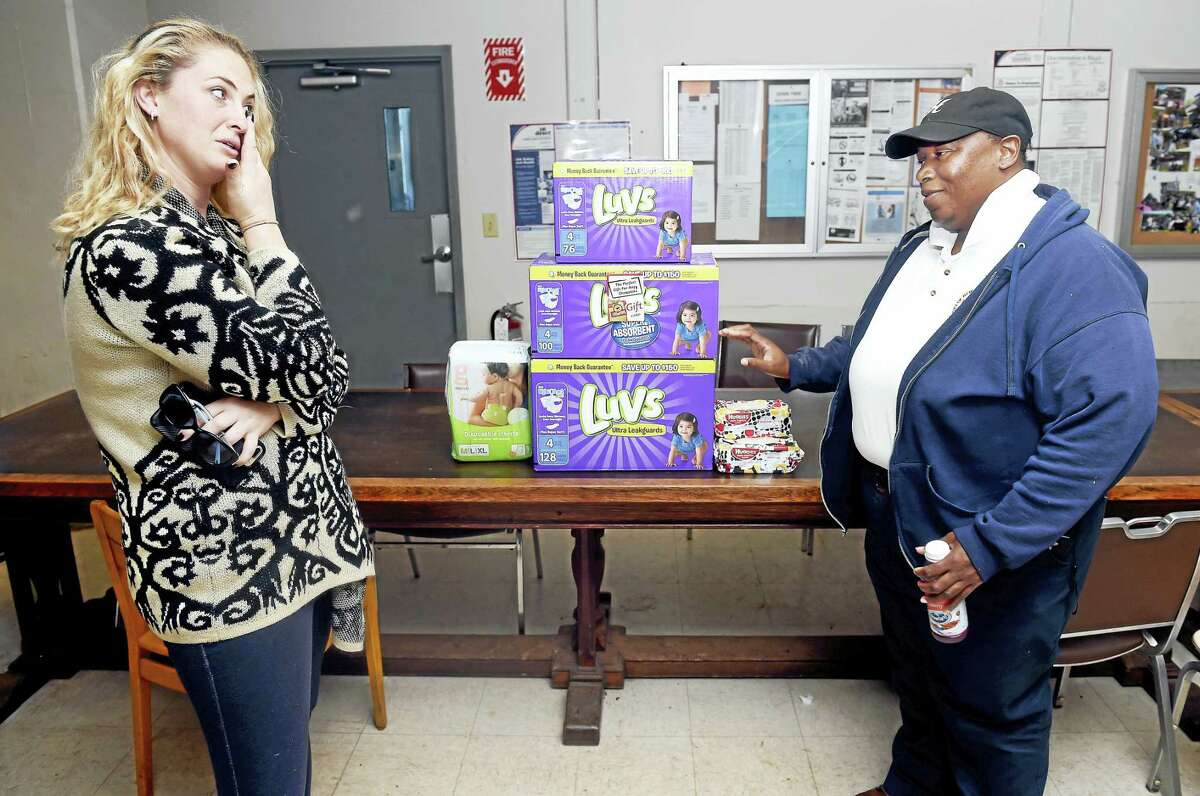 Kelly Soter, left, of Milford, wipes away a tear as she is presented with diapers and a ShopRite Supermarket gift card by Honda Smith at the New Haven Public Works Department in New Haven on 10/14/2016. Smith spearheaded this Act of Kindness with the help of her fellow Public Works Department employees who donated money for the effort.
