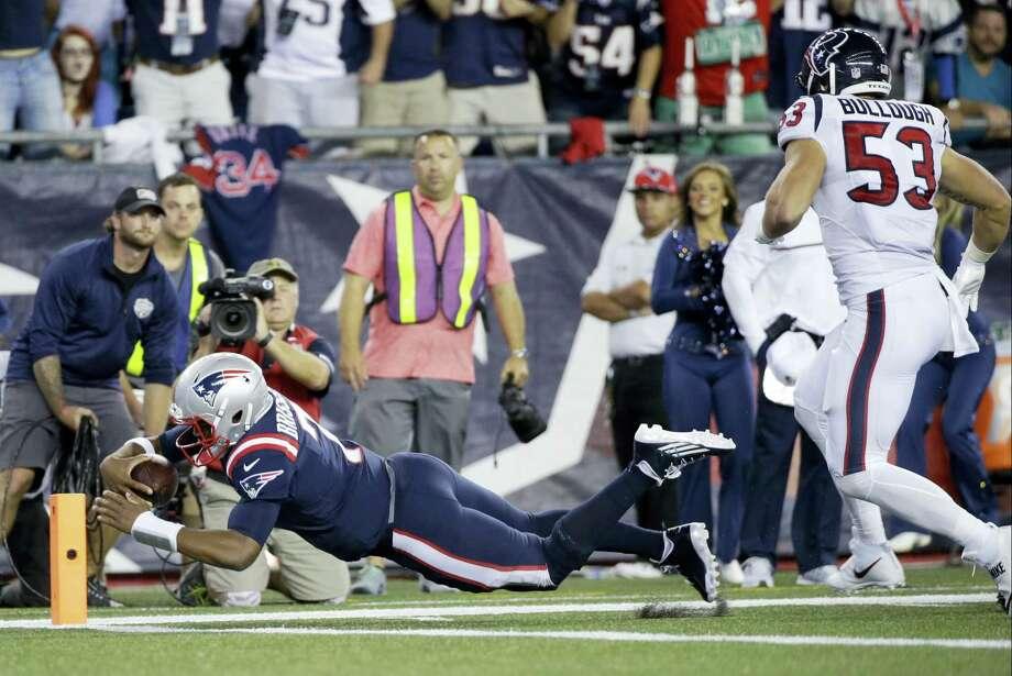 Patriots quarterback Jacoby Brissett (7) dives past Houston Texans linebacker Max Bullough (53) for a touchdown during the first half on Thursday. Photo: Elise Amendola — The Associated Press   / AP