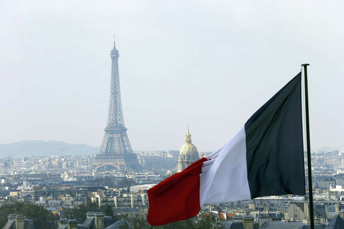 In this April 1, 2016, file photo, the French flag above the skyline of the French capital with the Eiffel Tower, The Invalides Dome and roof tops are seen from the colonnade of the Pantheon Dome in Paris. The Eiffel Tower, normally open every day of every year, is closed Tuesday Dec.13, 2016, because of a strike over salaries and working conditions.