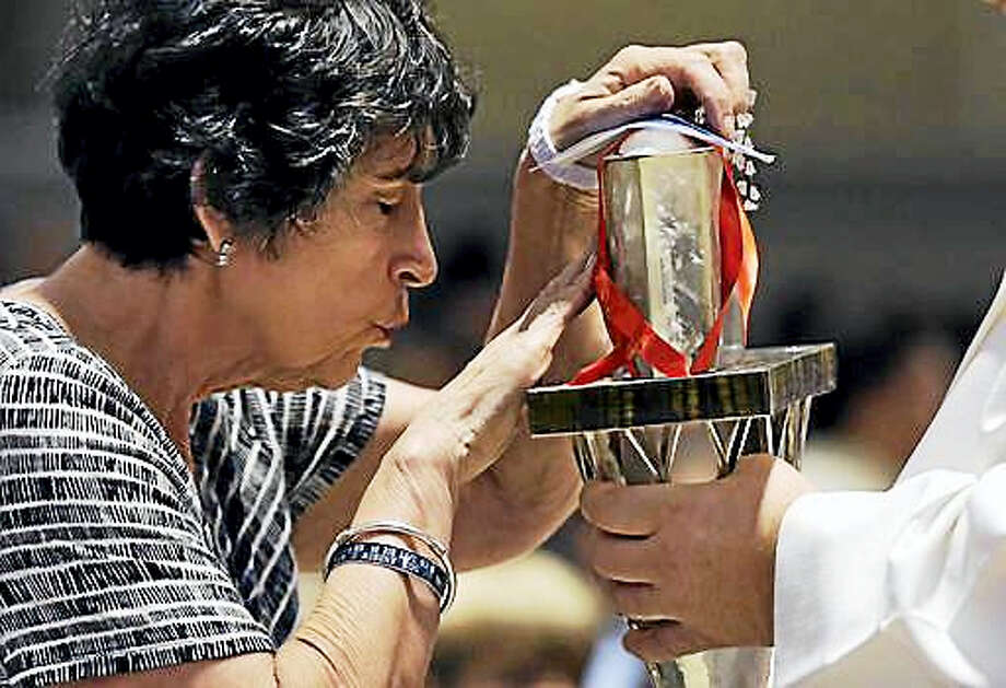 The heart of St. Padre Pio held in a plastic box by a priest is touched by a woman at the Immaculate Conception Church, Wednesday, Sept. 21, 2016, in Lowell, Mass. This marks the first time the religious relic has ever left its home in Italy. Photo: AP Photo/Elise Amendola    / AP