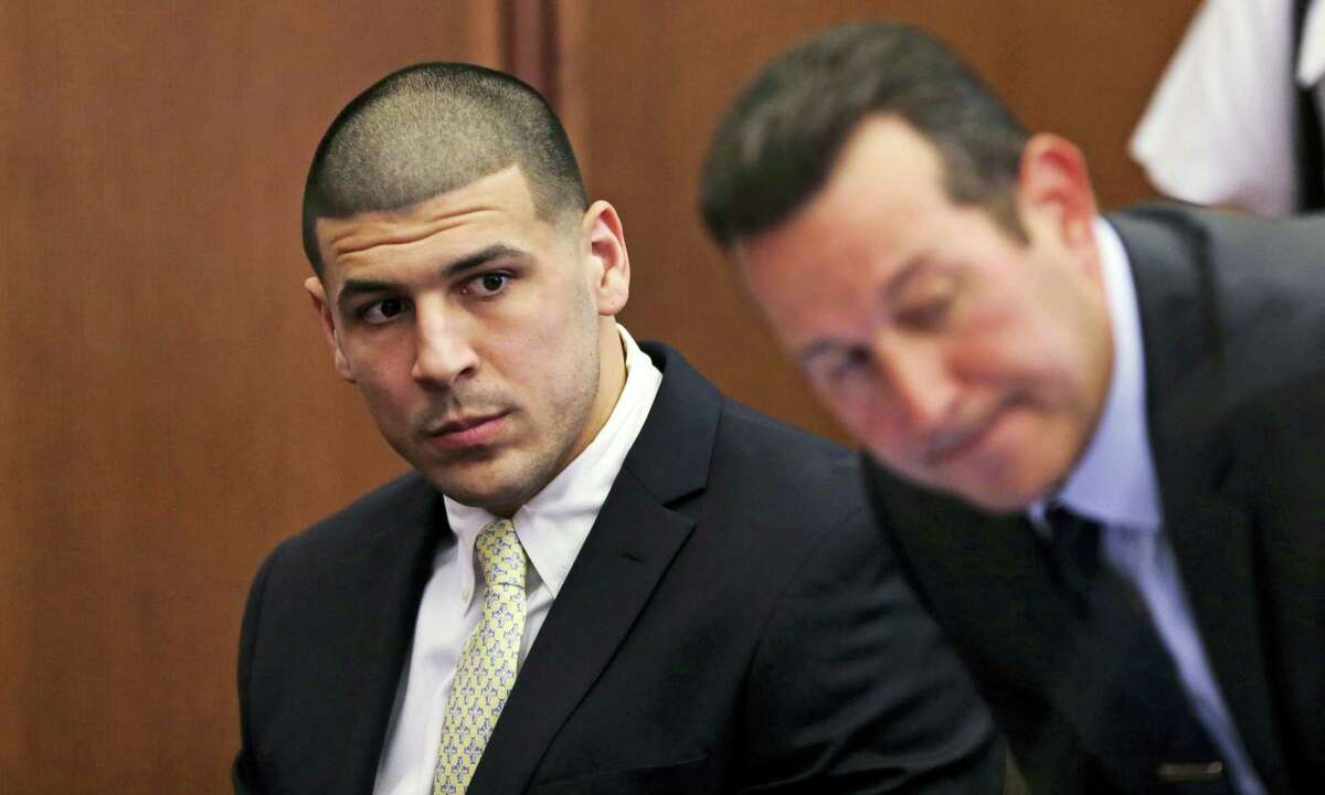 Former New England Patriots wide receiver Aaron Hernandez, left, looks down the table at his legal team as his new defense attorney Jose Baez, right, takes a seat during a court appearance at Plymouth Superior Court, Thursday in Plymouth, Mass.
