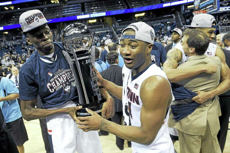 UConn center Amida Brimah, left, and guard Rodney Purvis (44) celebrate with the championship trophy in the finals of the American Athletic Conference men's tournament this past March. Photo: The Associated Press File Photo   / FR121174 AP