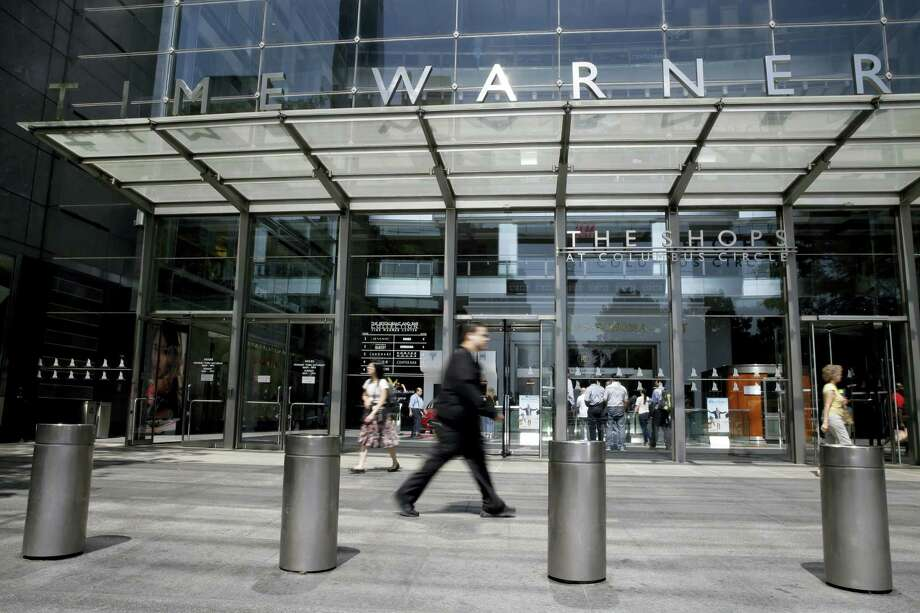 In this May 26, 2015 photo, pedestrians walk by an entrance to the Time Warner Center in New York. On Oct. 22, 2016, several reports citing unnamed sources said AT&T is in advanced talks to buy Time Warner, owner of the Warner Bros. movie studio as well as HBO and CNN. Photo: AP Photo/Mary Altaffer   / Copyright 2016 The Associated Press. All rights reserved.