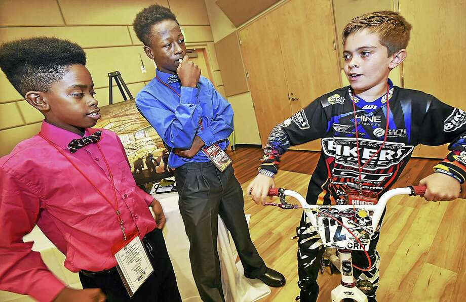 New Haven summer residents Amare Burruss, 14, of Maryland, and Devon Atkinson, 14, of North Carolina, talk to 10-year old BMX expert rider Zachary Michael Tuohy, of Belchertown, Mass., Thursday at the The Everybody Plays Foundation capital campaign kickoff unveiling the Centric Sports & Cycling Center to the New Haven community. Photo: Catherine Avalone — New Haven Register   / New Haven RegisterThe Middletown Press