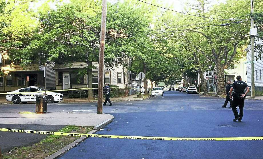The intersection of Shelton and Read streets was shut down and New Haven police were investigating after a shooting that wounded a woman, 59. Police say she was in a nearby home when she was hit by stray gunfire. Photo: Wes Duplantier — New Haven Register
