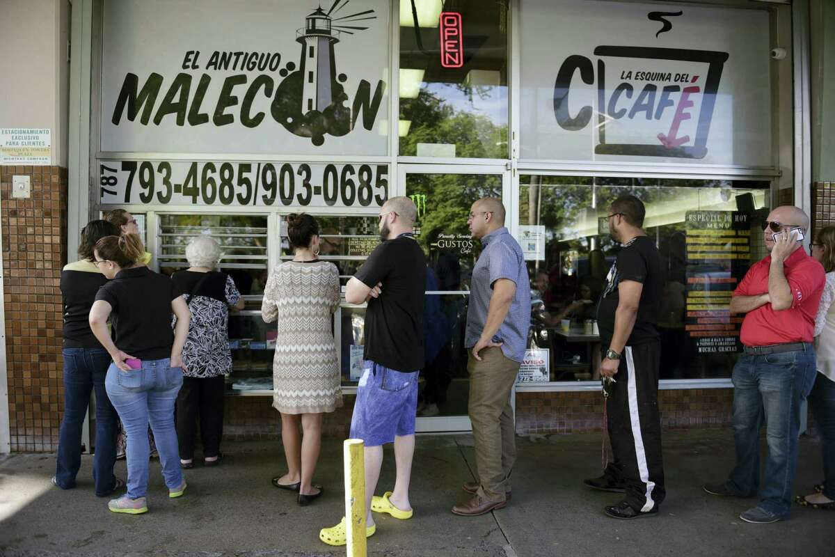 Customers stand in line at one of the few open cafeterias on Roosevelt Avenue, in San Juan, Puerto Rico on Sept. 22, 2016 after a massive blackout hit the island Wednesday afternoon, leaving at least 1.5 million people without power overnight and into the following day.