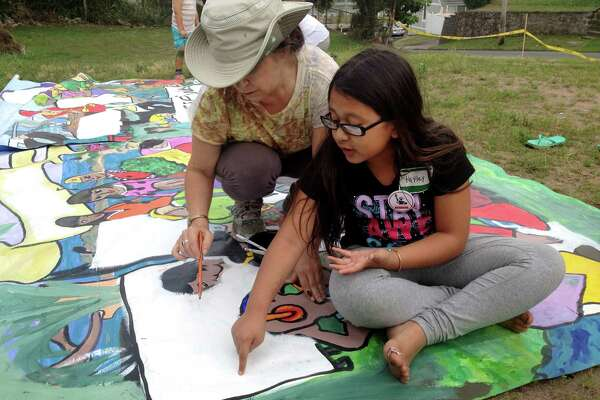Hayley Chavarria, 9, the youngest child of Nury Chavarria, works on a mural prior to a vigil held on Sunday, July 23, 2017, at Iglesia de Dios Pentecostal Church in New Haven, Conn. Nury Chavarria, who was supposed to be deported to Guatemala, has taken sanctuary at the church where she awaits her fate as the community rallies behind her.