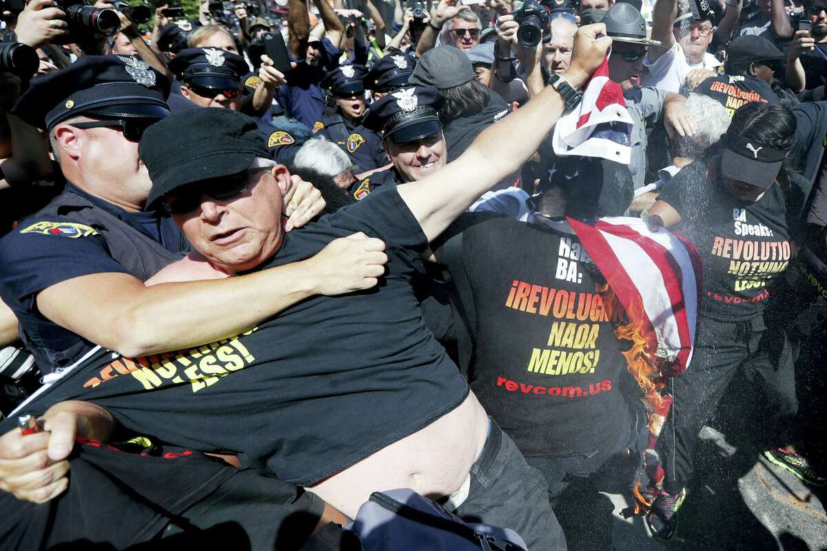 A law enforcement officer clashs with a protester who is holding a burning American flag Wednesday, July 20, 2016, in Cleveland, during the third day of the Republican convention.
