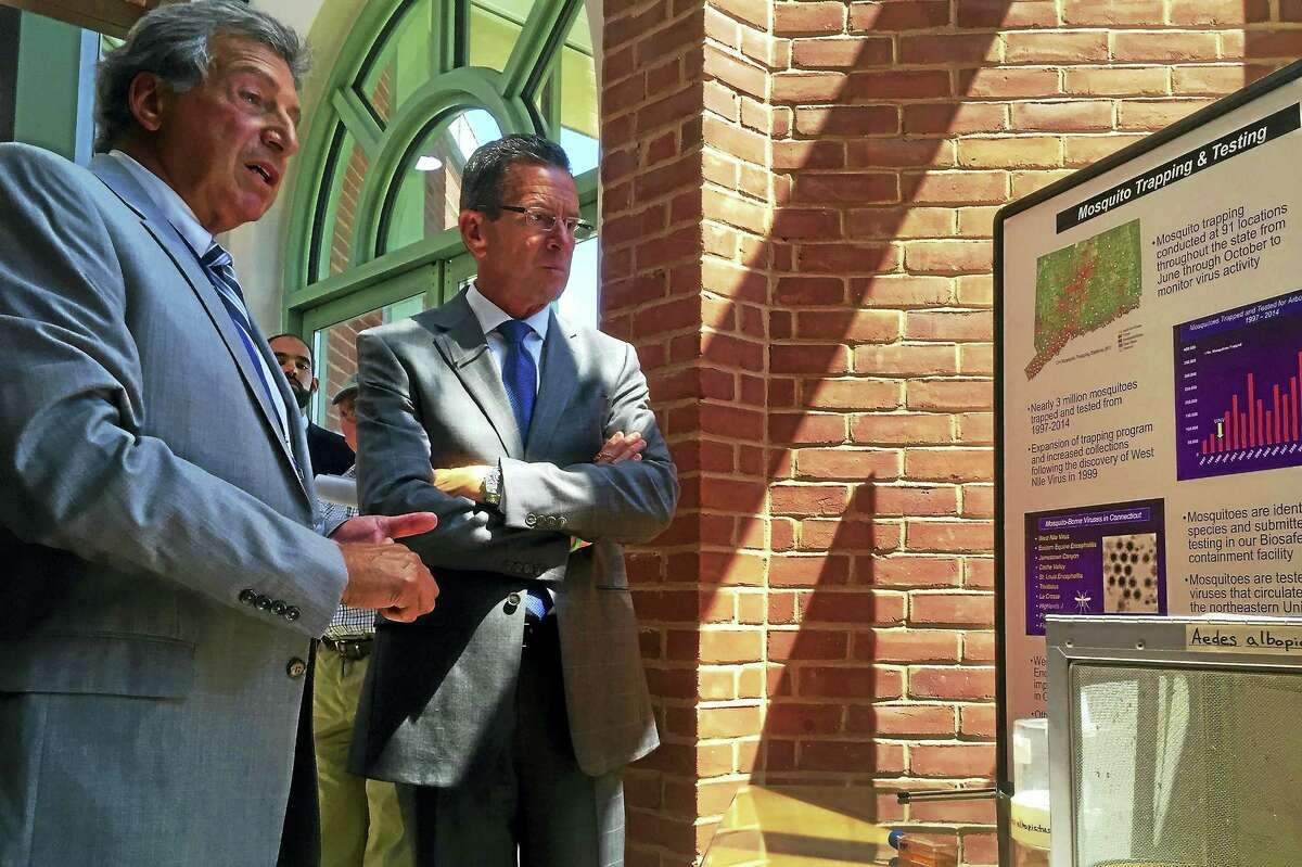 Theodore G. Andreadis, director of the Connecticut Agricultural Experiment Station, shows Gov. Dannel Malloy a display with images and text detailing mosquito testing after a press conference Thursday at the Experiment Station in New Haven.