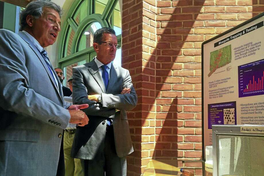 Theodore G. Andreadis, director of the Connecticut Agricultural Experiment Station, shows Gov. Dannel Malloy a display with images and text detailing mosquito testing after a press conference Thursday at the Experiment Station in New Haven. Photo: Esteban L. Hernandez — New Haven Register