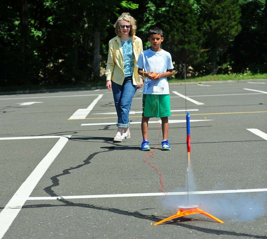 College for Kids program teacher Heather Cochrane watches as student Mattias Rivera, 10, launches a rocket Friday at Norwalk Community College in Norwalk. With half-day, week-long classes through July 31, the program is designed to offer kids from around the area a dive into different academic subjects in interactive and engaging ways. Photo: Erik Trautmann / Hearst Connecticut Media / Norwalk Hour