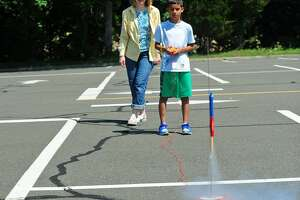 College for Kids program teacher Heather Cochrane watches as student Mattias Rivera, 10, launches a rocket Friday at Norwalk Community College in Norwalk. With half-day, week-long classes through July 31, the program is designed to offer kids from around the area a dive into different academic subjects in interactive and engaging ways.