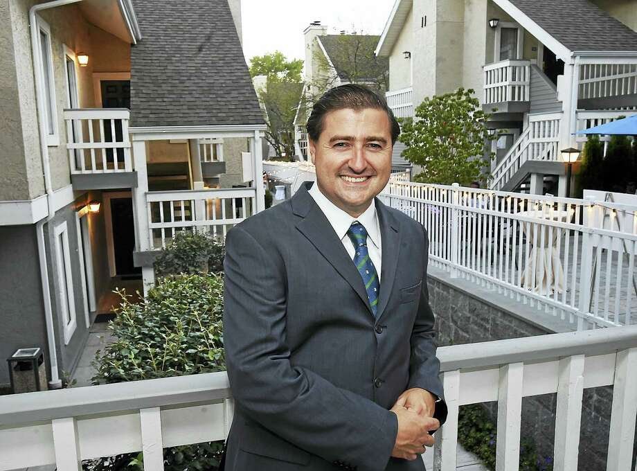Juan Salas-Romer, managing partner at NHR Properties, near the upper veranda at the New Haven Village Suites Thursday on Long Wharf Drive in New Haven. Photo: Catherine Avalone — New Haven Register   / New Haven RegisterThe Middletown Press