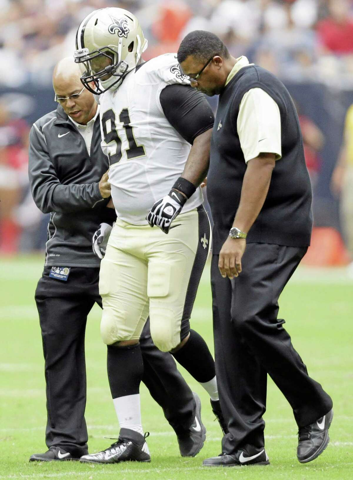 New Orleans Saints linebacker Will Smith (91) is helped off the field during the first half of a preseason NFL football game against the Houston Texans on Aug. 25, 2013, in Houston.