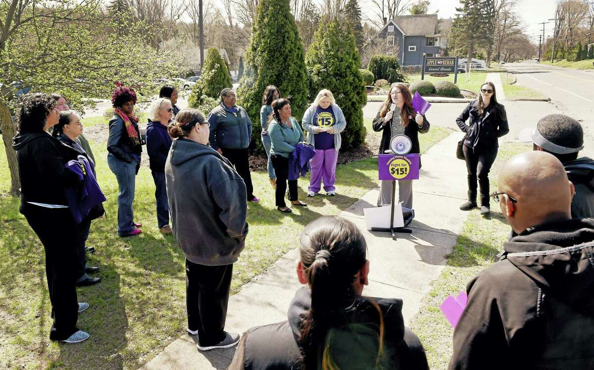 """Suzanne Clark, vice-president of the New England Health Care Employees Union SEIU local 1199 of Hartford, speaks to union workers as they rally for higher wages Thursday, April 14, 2016 during the SEIU's National Day of Action for """"Fight for 15"""" campaign in front of Apple Rehab Laurel Woods in East Haven, a non-union short-term rehabilitation facility."""