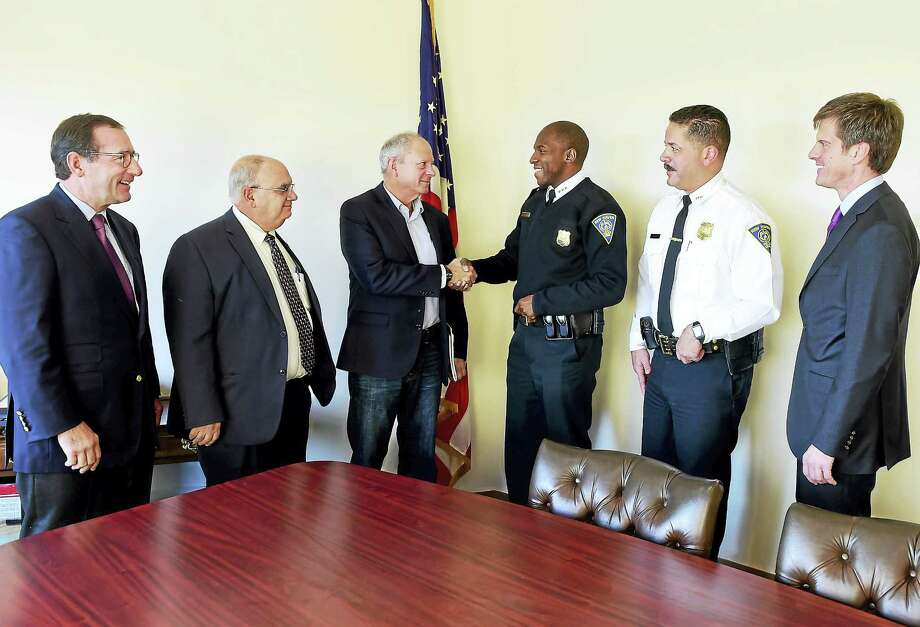 Faxon Law Group partners Timothy Pothin, far left, and Eric Smith, far right, with Assistant New Haven Police Chiefs Achilles Generoso, second from left, and Luiz Casanova, second from right, watch as Acting New Haven Police Chief Anthony Campbell shakes hands with Dan Zimmerman, founder of LiveKinds's Cops and Kids Program at the New Haven Police Department. Photo: Peter Hvizdak — New Haven Register   / ©2016 Peter Hvizdak